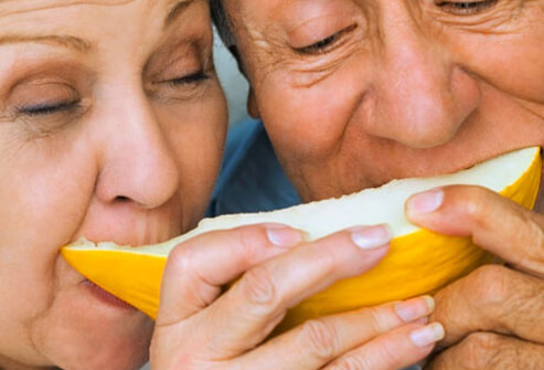 An elderly couple shares a slice of melon.