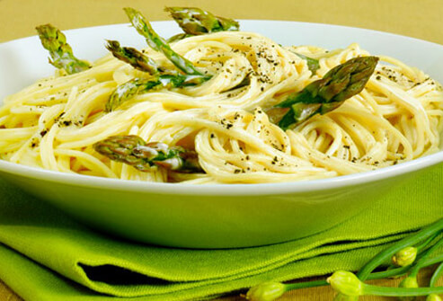 A bowl of pasta with asparagus.